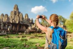 Weibliches touristisches nehmendes Bild von Bayon-Tempel in Angkor Thom Lizenzfreie Stockbilder