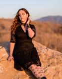 Weibliches tragendes Spitzekleid des Brunette auf dem Gebiet Lizenzfreie Stockbilder