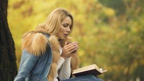 Weibliches trinkendes Erwärmungsgetränk von der Thermosflascheschale während Ablesenbuch, Einsamkeit stock video footage