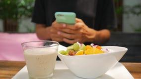 Weibliches Twxting mit Handy während ihres gesunden Frühstücks-Abschlusses des strengen Vegetariers oben von ein junges Mädchen-H stock footage