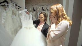 Weibliches Versuchen auf Hochzeitskleid in einem Shop mit den Frauen behilflich stock video
