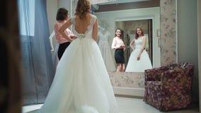 Weibliches Versuchen auf Hochzeitskleid in einem Shop mit den Frauen behilflich stock video footage