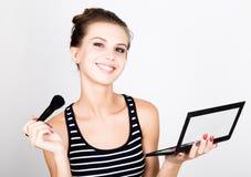 Weibliches vorbildliches zutreffendes Make-up auf ihrem Gesicht Schöne junge Frau, die Grundlage auf ihrem Gesicht mit einer Bild Stockfoto