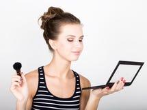 Weibliches vorbildliches zutreffendes Make-up auf ihrem Gesicht Schöne junge Frau, die Grundlage auf ihrem Gesicht mit einer Bild Lizenzfreie Stockfotografie