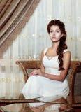 Weiblichkeit. Brown-Haar-Frauen-Braut im Hochzeits-Kleidersitzen. Klassischer romantischer Innenraum Stockfotos