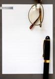 Weißbuch im grauen Rahmen mit Stift und Sonnenbrille Lizenzfreies Stockbild
