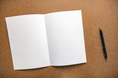 Weißbuchanmerkung und -stift auf hölzernem Schreibtisch des Geschäfts mit Kopienraum Stockfoto