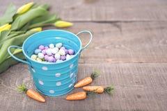 Weiche Pastenszene des blauen Eimers mit Süßigkeitseiern, kleine Karotten a Stockfotos