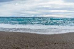 Weiche und leichte Wellen schäumen in blauer Ozeanitalien-Küste, Sommervorabend Stockfotos