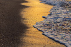 Weiche Welle auf dem Strand bei dem Sonnenuntergang, der goldene Farben schafft Lizenzfreies Stockfoto