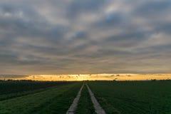 Weiche Wolken mit Wellen und Wogen über der niederländischen Landschaft bei Sonnenuntergang stockbild