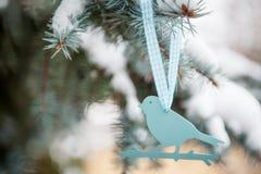 Weicher blauer Plastikvogel auf einem schneebedeckten Baum Stockbild