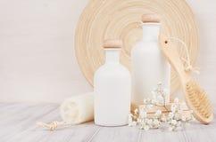 Weicher eleganter Badezimmerdekor, Schablone von weißen Kosmetikflaschen mit Kamm, Blumen auf weißem hölzernem Brett, Kopienraum stockbild
