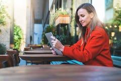 Weicher Fokus Lächelnde attraktive Frau der Junge im orange Mantel sitzt draußen im Café bei Tisch und benutzt Tablet-Computer Lizenzfreies Stockbild