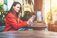 Weicher Fokus Lächelnde attraktive Frau der Junge im orange Mantel sitzt draußen im Café bei Tisch und benutzt Tablet-Computer Lizenzfreies Stockfoto