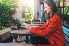 Weicher Fokus Lächelnde attraktive Frau der Junge im orange Mantel sitzt draußen im Café bei Tisch und benutzt Tablet-Computer Stockfotos
