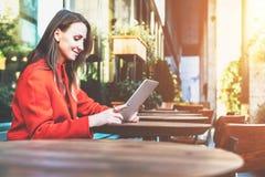 Weicher Fokus Lächelnde attraktive Frau der Junge im orange Mantel sitzt draußen im Café bei Tisch und benutzt Tablet-Computer Stockbild