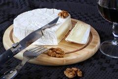 Weicher französischer Käse Coulommiers, Walnüsse und ein Glas Rotwein lizenzfreie stockfotografie