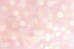 Weicher Pastellrosahintergrund Bokeh mit unscharfen goldenen Lichtern Stockfotografie