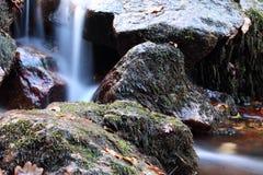 Weicher Wasserfall mit Felsen im Wald in der langen Belichtung Stockbilder