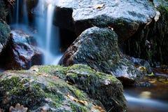 Weicher Wasserfallfluß mit Felsen im Wald in der langen Belichtung Stockbild