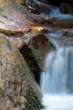 Weicher Wasserfallfluß mit Felsen im Wald in der langen Belichtung Lizenzfreies Stockfoto