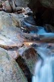 Weicher Wasserfallfluß mit Felsen im Wald in der langen Belichtung Lizenzfreie Stockbilder