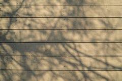 Weiches abstraktes natürliches Muster des großen Baumastschattens auf hellbraunem hölzernem Plankenstreifenkorngefüge-Oberflächen Lizenzfreie Stockbilder