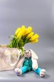 Weiches Spielzeug in den Geschenktaschen und in den gelben Tulpen Stockbilder