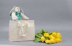 Weiches Spielzeug in den Geschenktaschen und in den gelben Tulpen Lizenzfreie Stockbilder