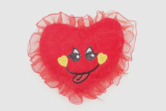 Weiches Spielzeug im Liebesherzen mit nettem Gesicht Lizenzfreie Stockfotografie
