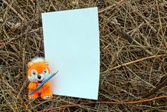 Weiches Spielzeug mit einem Bleistift und einem Blatt Papier auf trockenen Anlagen Lizenzfreie Stockfotografie