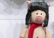 Weiches Spielzeugschwein in einem Pelzhut stockbild