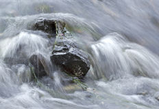 Weiches Wasser, das über Felsen hetzt lizenzfreie stockfotografie