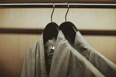 Weichzeichnung bei der Robe zwei, die am Gestell in der Garderobe hängt stockbild