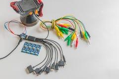 Weichzeichnung das Vielzweckladegerät, Leiterplatte, Netzanschlusskabel, Vielzweck, Mechanikerwerkzeug, Pinzette mit elektrischem Stockbilder