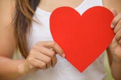 Weichzeichnung der Frau hält handgemachtes großes rotes Herzpapier lizenzfreie stockfotos