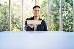 Weichzeichnung des jungen Geschäftsmannes Sitting am Tisch im Büro durch Glasfenster Freundlicher junger Mann übergab ein Dokumen lizenzfreie stockfotos