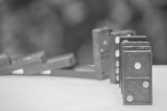 Weichzeichnung - Domino-Effekt-Konzept: Reihe von schwarzen Dominos auf weißem Boden und bokeh Hintergrund Lizenzfreie Stockbilder