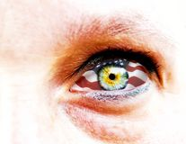 Weichzeichnung und Abschluss oben eines grünen Auges der gelben Frau auf einem weißen Hintergrund mit USA-Flagge in der Iris Lizenzfreie Stockfotografie