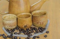 Weichzeichnungsbild von den Kaffeebohnen und von Kaffeetassen eingestellt Stockfotos