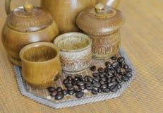 Weichzeichnungsbild von Kaffeebohnen und von Kaffeetassen stellte auf hölzernes b ein Lizenzfreie Stockfotografie