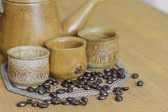 Weichzeichnungsbild von Kaffeebohnen und von Kaffeetassen stellte auf hölzernes b ein Stockfoto