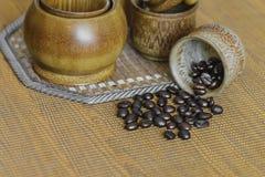 Weichzeichnungsbild von Kaffeebohnen und von Kaffeetassen stellte auf hölzernes b ein Lizenzfreies Stockbild