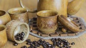 Weichzeichnungsbild von Kaffeebohnen und von Kaffeetassen stellte auf hölzernes b ein Stockbilder