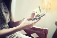 Weichzeichnungsfrauenasiat, der das intelligente Telefon- und Kreditkarteeinkaufen verwendet stockfotos