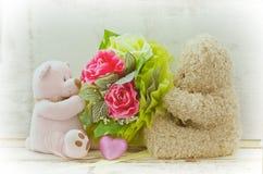 Weichzeichnungspaare von den netten Bären, die Rosenblumenstrauß halten stockfotos