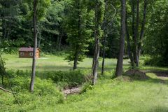 Weide met kleine cabine en stroom stock foto's