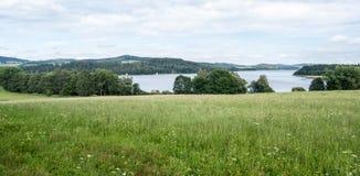Weide met Lipno-waterreservoir en heuvels op de achtergrond royalty-vrije stock foto's