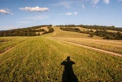 Weide met weg, fotograafschaduw, heuvel op de achtergrond en blauwe hemel met wolken Royalty-vrije Stock Afbeeldingen